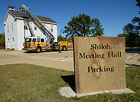 Ron Skelton (top), an assistant chief for the Springdale Fire Department, operates a ladder truck Tuesday, Oct. 13, 2020, to position Curtis Morris, exhibits manager for the Shiloh Museum of Ozark History, near the bell tower of the Shiloh Meeting Hall in Springdale so he can replace the mechanism that is used to ring the bell in the historic building. The original pre-Civil War-era bell is being curated in the museum's collection and a replacement has been fitted to the bell tower, but the mechanism to ring it needed to be improved. Visit nwaonline.com/201014Daily/ for today's photo gallery. <br /> (NWA Democrat-Gazette/Andy Shupe)