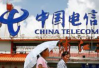 Pedestrians walk past a China Telecom sign in Shanghai, China..