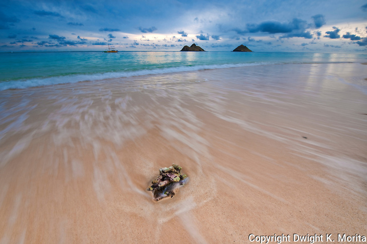 Receding wave at dawn on Lanikai Beach with the Mokulua Islands in the background.