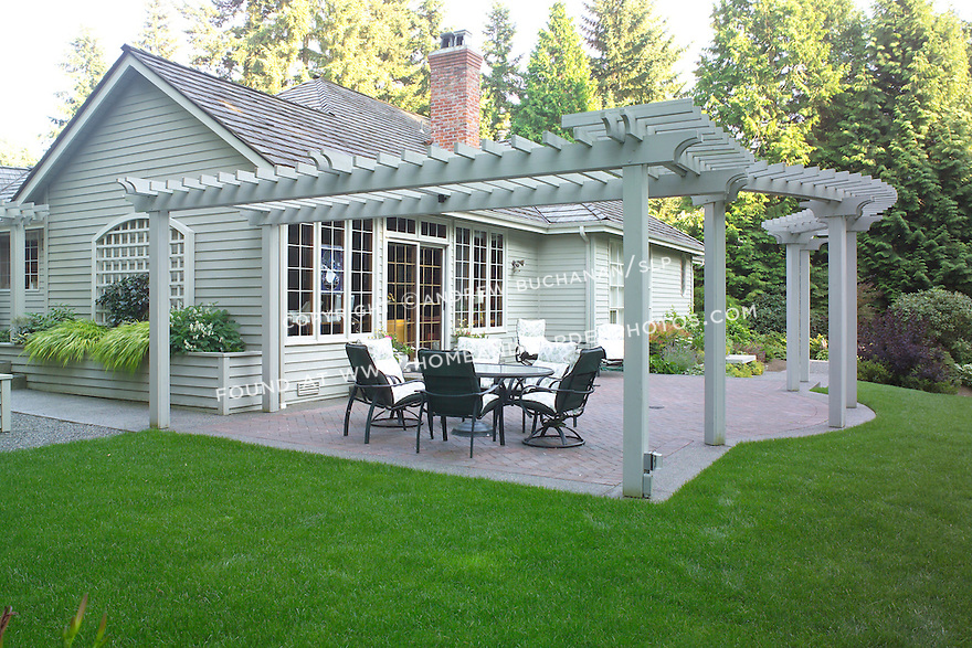 A decorative brick patio topped by a curving arbor off the rear of this suburban home near Seattle opens to a large, well-groomed backyard with a large expanse of grass on a slope, and surrounded and interesected with beds and borders of mixed trees and shrubs in a typical Northwest summer garden scene.