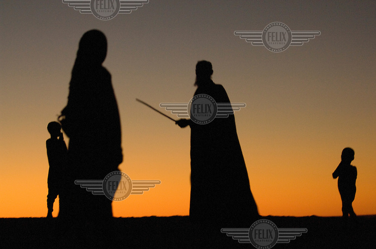 Silhouettes of Arab Moors living in the Sahara Desert town of Boujbeja. /Felix Features