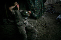 An exhausted American soldier at 'Restrepo' bunker. The position was named after a soldier from 2nd Platoon who was recently killed by insurgents..Battle Company, 2nd Battalion Airborne of the 503rd US Infantry are undergoing a 15 month deployment in the Korengal Valley, epicentre of the war and scene of fierce fighting with the Taliban...