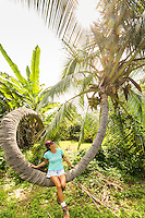 A woman sits on an unusual-looking curly palm tree in Kealakekua, Big Island.