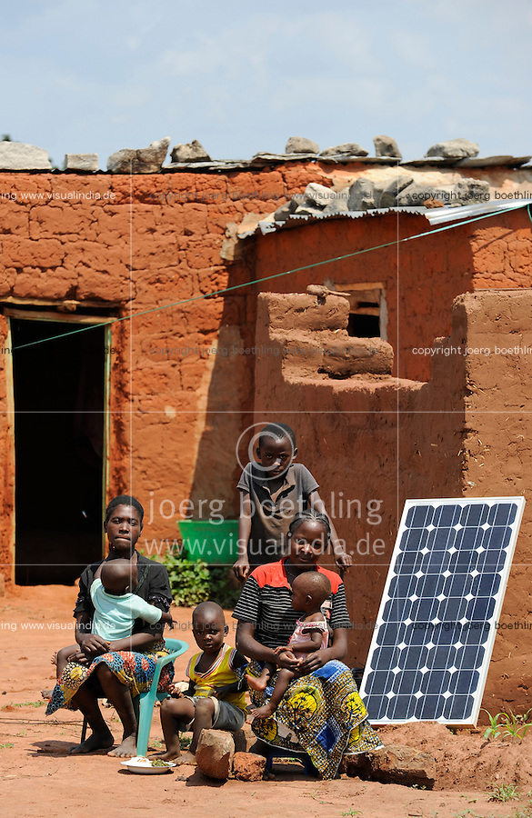Afrika ANGOLA Kwanza Sul, Dorf Cassombo, Familie mit Solarpanel vor ihrer Lehmhuette / ANGOLA Kwanza Sul, village Cassombo, family with solar panel in front of their hut