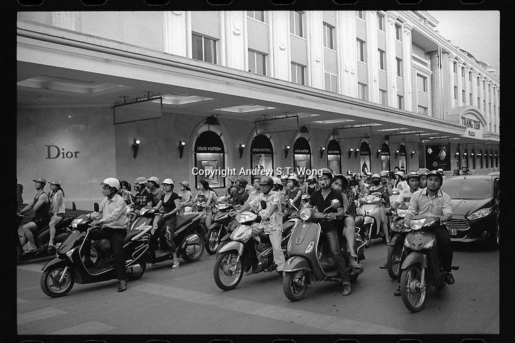 Vietnamese motorbike riders halt at a traffic light outside a shopping mall in Hanoi, Vietnam, June 2016.
