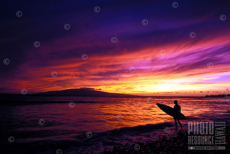 Surfer enjoys a West Maui sunset after surfing at Olowalu, Maui.