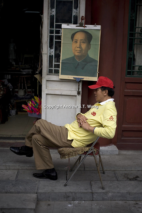 BEIJING, CHINA - SEPTEMBER 30: A Beijing resident sit outside a shop at an old alleyway, or hutong, decorated with a portrait of the founder of the Communist China Mao Zedong, as he takes part in a voluntary scheme to monitor his neighbourhood to ensure the safety of tomorrow's National Day celebration on September 30, 2009 in Beijing, China. Chinese people are in preparation for the upcoming National Day on October 1, 2009 which will commemorate the 60th anniversary of the founding of the People's Republic of China.