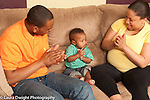 Baby boy 10 months old at home with parents clapping game