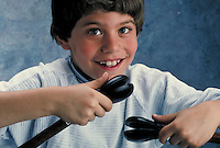 Smiling boy looking into the camera and playing the castanets.  May not be used in an elementary school dictionary.