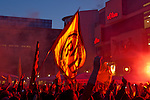 On the ancient marketplace in Dortmund fans celebrate a party because of the title win of their favorite soccer club BVB 09 in the German Premium League. Here they are waving flags and display bengal fireworks.
