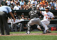 Ramon Castro #27 of the Chicago White Sox tags out Jake Fox #9 of the Baltimore Orioles during a MLB game at Camden Yards, on August 8 2010, in Baltimore, Maryland. Orioles won 4-3.