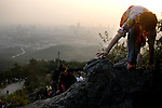 People climb up a rock face at the top of the Purple-Gold Mountain in the outskirts of Nanjing, China.