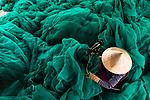 Fishermen repair large fishing net by Olivier Apicella