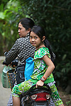 A young girl on the back of a motorbike turns to smile at a lone foreigner out for a morning stroll in the Mekong Delta near My Tho, Vietnam. Oct. 3, 2011.