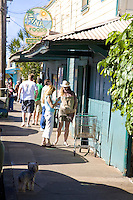 People walking and standing on the sidewalk outside of Mana Foods grocery store in Paia, Maui