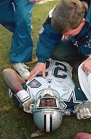 SAN FRANCISCO, CA - Running back Emmitt Smith of the Dallas Cowboys lies on the ground hurt during the NFC Championship Game against the San Francisco 49ers at Candlestick Park in San Francisco, California in 1995. Photo by Brad Mangin
