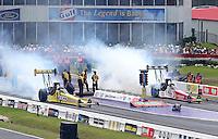 Apr. 28, 2013; Baytown, TX, USA: NHRA top fuel dragster driver Morgan Lucas (left) burns out alongside Doug Kalitta during the Spring Nationals at Royal Purple Raceway. Mandatory Credit: Mark J. Rebilas-