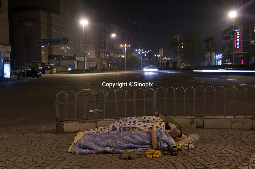 Panicky Chengdu residents sleep on street at night after an aftershock alert by the Sichuan seismological bureau which warned there was high probability of an aftershock between 19 May & 20 May. The 8 magnitude earthquake happened at 14:28pm on 12 May 2008, with the epicenter in Wenchuan County, about 159km NW of Chengdu, Sichuan, China.