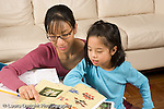 8 year old girl at home doing homework for Chinese language class,helped by mother horizontal.EVOstock