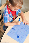 Education preschool 3-4 year olds art activty boy drawing letters with marker vertical