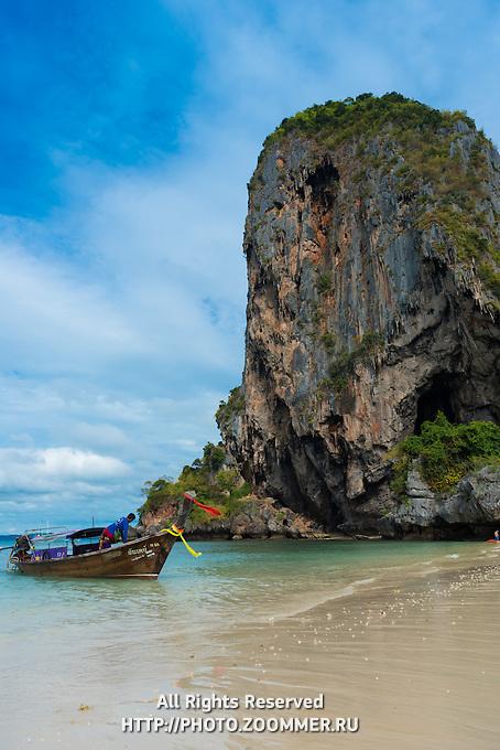 Longtail boat near a rock on Phra Nang beach in Krabi, Thailand