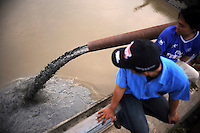 People watch mud from the Lapindo mud flow lake being pumped into the Porong River. Since May 2006, more than 10,000 people in the Porong subdistrict of Sidoarjo have been displaced by hot mud flowing from a natural gas well that was being drilled by the oil company Lapindo Brantas. The torrent of mud - up to 125,000 cubic metres per day - continued to flow three years later.