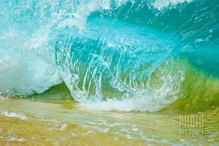 A beautiful closeup of a wave barreling as it crashes onto the sand at Ke Iki Beach, on the North Shore of Oahu.