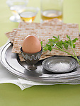 Ingredients for a Passover plate–brown egg, matzo bread, parsley sprig, and sea salt. <br /> On a metal plate against a white cloth napkin and green background, with drinks behind it