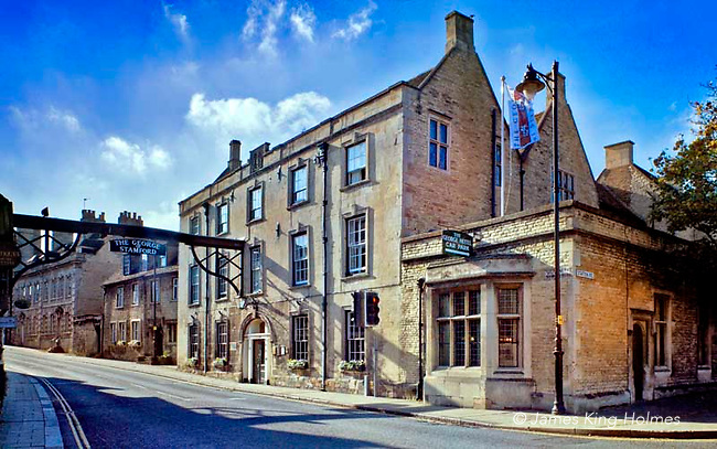 Old coaching inn, the George Hotel at the side of the old Great North Road, an old turnpike road in Stamford, Lincolnshire, UK. A wooden bar stradling the road carries the hotel's name and symbolizes a gallows, as a warning to 18th Century highwaymen that they were not welcome and would be turned in to the law.