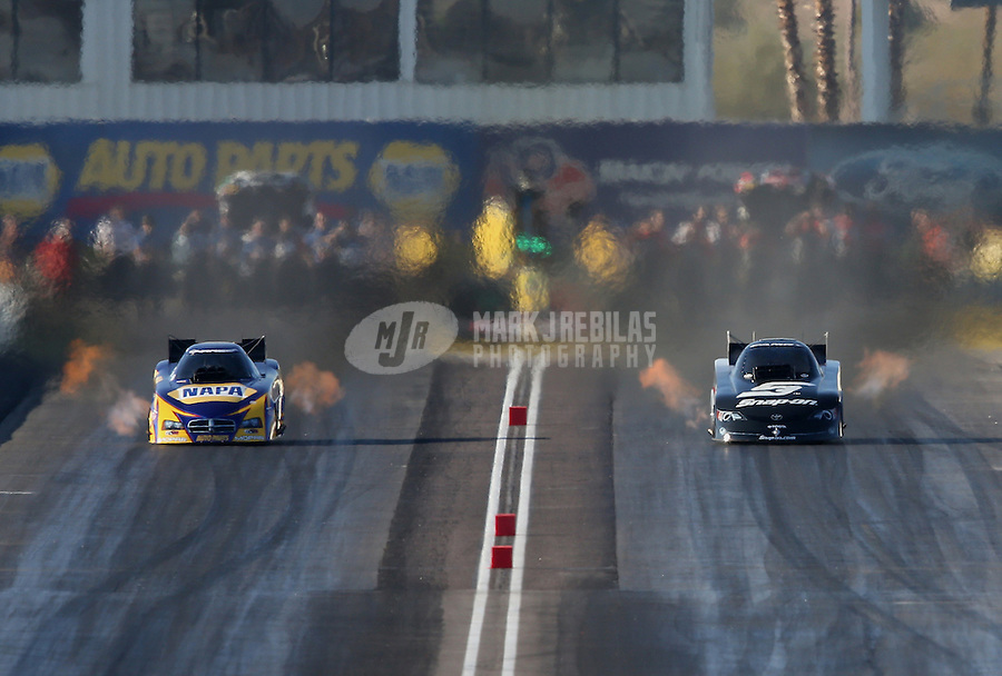 Feb. 23, 2013; Chandler, AZ, USA; NHRA funny car driver Cruz Pedregon (right) races alongside Ron Capps during qualifying for the Arizona Nationals at Firebird International Raceway. Mandatory Credit: Mark J. Rebilas-