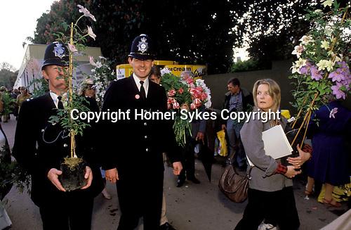 Policeman, Chelsea Flower Show, carrying shrubs 1980s UK