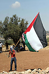 A masked palestinian lifts his country flag during a demonstration against Israel's controversial separation barrier in the West Bank village of Nilin, near Ramallah. Five Palestinians were wounded today as Israeli soldiers fired rubber bullets at demonstrators protesting at the construction of a separation wall on the outskirts of Nilin, medics said.