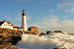This photograph captures the power and beauty of the Atlantic Ocean as it comes to shore after a wild storm at Portland Head Light, Cape Elizabeth, Maine. The wave is echoed by a lovely blue sky with pretty clouds whose whiteness and form is so similar to the water. Also seen is the end of another wave that is cascading down the large rocks that protect the lighthouse.