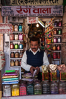 Jaipur, Rajasthan, India.  Shopkeeper Selling Glitter and other Coloring Agents for Decorative Purposes.