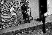 Armed policemen patrol in the gang neighborhood in San Salvador, El Salvador, 12 May 2011. During the last two decades, Central America has become the deadliest region in the world that is not at war. According to the UN statistics, more people per capita were killed in El Salvador than in Iraq, in recent years. Due to the criminal activities of Mara Salvatrucha (MS-13) and 18th Street Gang (M-18), the two major street gangs in El Salvador, the country has fallen into the spiral of fear, violence and death. Thousands of Mara gang members, both on the streets or in the overcrowded prisons, organize and run extortions, distribution of drugs and kidnappings. Tattooed armed young men, mainly from the poorest neighborhoods, fight unmerciful turf battles with their coevals from the rival gang, balancing between life and death every day. Twenty years after the devastating civil war, a social war has paralyzed the nation of El Salvador.