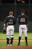 West Virginia Black Bears catcher Arden Pabst (52) and relief pitcher Yunior Montero (48) stand on the mound for God Bless America during the seventh inning stretch during a game against the Batavia Muckdogs on June 29, 2016 at Dwyer Stadium in Batavia, New York.  West Virginia defeated Batavia 9-4.  (Mike Janes/Four Seam Images)