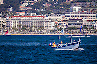 "Europe/France/Provence-Alpes-Côte d'Azur/Alpes-Maritimes/Cannes:  Le Front de Mer, la Croisette et l'Hôtel Carlton   avec un pointu  //    Europe, France, Provence-Alpes-Côte d'Azur, Alpes-Maritimes, Cannes: Cannes: The Waterfront, the Croisette and the Carlton Hotel with a pointu,  The ""Pointu"" is a traditional fishing boat of the Mediterranean Sea."
