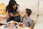 2 year old toddler boy with mother talking and gesturing playing with blocks