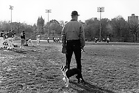 USA. New York. Central Park. A man with a basebal glove and a cigar holds a boxer dog on a leash. American football players are dressing up before the start of their game. © 1986 Didier Ruef