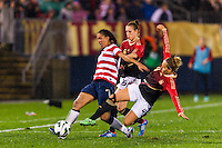 Shannon Boxx (7) of the United States (USA) passes the ball as Babett Peter (4) of Germany (GER) comes in for a tackle. The United States (USA) and Germany (GER) played to a 2-2 tie during an international friendly at Rentschler Field in East Hartford, CT, on October 23, 2012.