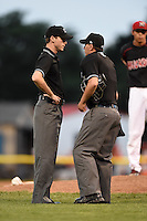 Umpires Brandin Sheeler (left) and Anthony Perez discuss a call during a game between the Brooklyn Cyclones and Batavia Muckdogs on August 11, 2014 at Dwyer Stadium in Batavia, New York.  Batavia defeated Brooklyn 4-3.  (Mike Janes/Four Seam Images)