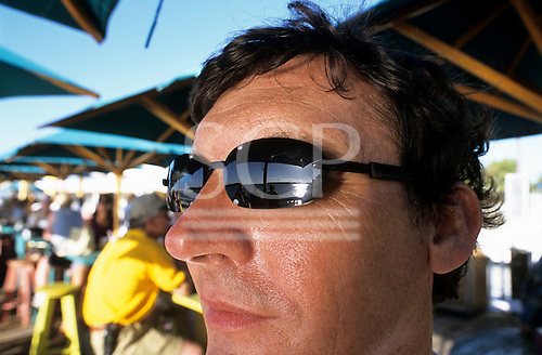 Key West, Florida, USA. Man in bar wearing sunglasses with silver sunlight and sea reflecting in them.