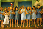 Junior school children end of term play, children up on stage clapping. Private education 1990s Kent UK