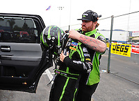 Nov. 10, 2011; Pomona, CA, USA; NHRA funny car driver Alexis DeJoria puts on safety equipment with the help of a crew member during qualifying at the Auto Club Finals at Auto Club Raceway at Pomona. Mandatory Credit: Mark J. Rebilas-
