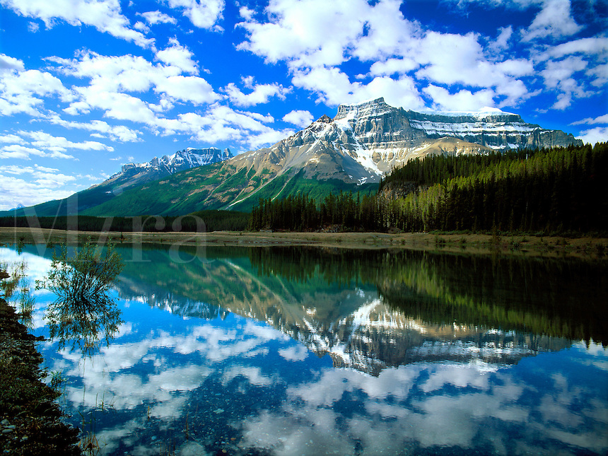Art in Nature 9607-0113 - Lake reflecting clouds, wide blue sky and mountain range in Banff National Park. Alberta, Canada.