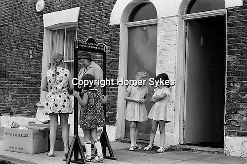 FERN STREET SETTLEMENT,<br /> BOW, LONDON 1973<br /> <br /> Irene Wood giving out the Farthing Bundles. <br /> <br /> The turn of the century saw the<br /> founding of a number of<br /> settlements in the poorest parts<br /> of London. The Fern Street Settlement was founded on behalf of the Devon's<br /> Junior School in 1907 by the school's<br /> headmistress and warden, Miss<br /> Clara Grant. She therefore started an<br /> imaginative scheme known as<br /> 'farthing bundles'. Any child<br /> who had a farthing and could<br /> walk under a wooden arch forty-<br /> eight inches high without<br /> stooping received a bundle.<br /> These usually contained note-<br /> pads, pencils, small toys, pieces<br /> of string, etc. Over the arch she<br /> had painted: 'Enter all ye<br /> children small, none can come<br /> who are too tall.' Taller children<br /> had to pay a penny for their<br /> bundle. Inflation and the welfare state have modified the custom a little.<br /> The bundle has risen by stages to<br /> the price of a new half-penny,<br /> and today's taller children have a<br /> fifty-two-inch arch to go through<br /> every other Saturday;<br /> attendance is also down to<br /> between fifteen and thirty.