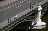 People crossing the Pont de Sully bridge over the Seine in Paris, France.