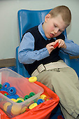 MR / Albany, NY.Langan School at Center for Disability Services .Ungraded private school which serves individuals with multiple disabilities.Boy works hard by himself at grasping colored gear shaped toys. Boy: 9, cerebral palsy, non verbal with expressive and receptive language delays.MR: Law4.© Ellen B. Senisi