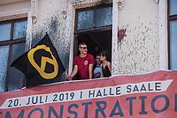 """Am Samstag den 20 Juli 2019 versuchten in Halle an der Saale ca. 200 Mitglieder und Anhaenger der rechtsextremen """"Identitaeren Bewegung"""", IB, eine Demonstration durchzufuehren. Sie versammelten sich dafuer vor dem Haus der IB in der Adam-Kuckhoff-Straße 16. Aufgrund von Gegenprotesten konnten die Rechtsextremen jedoch nicht marschieren, da alle Straßen um ihr Haus von Gegendemonstranten blockiert wurden.<br /> Im Bild: Ein Mitglied der """"Identitaeren"""" aus Daenemark, mit Fahne, am Fenster des IB-Haus.<br /> 20.7.2019, Berlin<br /> Copyright: Christian-Ditsch.de<br /> [Inhaltsveraendernde Manipulation des Fotos nur nach ausdruecklicher Genehmigung des Fotografen. Vereinbarungen ueber Abtretung von Persoenlichkeitsrechten/Model Release der abgebildeten Person/Personen liegen nicht vor. NO MODEL RELEASE! Nur fuer Redaktionelle Zwecke. Don't publish without copyright Christian-Ditsch.de, Veroeffentlichung nur mit Fotografennennung, sowie gegen Honorar, MwSt. und Beleg. Konto: I N G - D i B a, IBAN DE58500105175400192269, BIC INGDDEFFXXX, Kontakt: post@christian-ditsch.de<br /> Bei der Bearbeitung der Dateiinformationen darf die Urheberkennzeichnung in den EXIF- und  IPTC-Daten nicht entfernt werden, diese sind in digitalen Medien nach §95c UrhG rechtlich geschuetzt. Der Urhebervermerk wird gemaess §13 UrhG verlangt.]"""