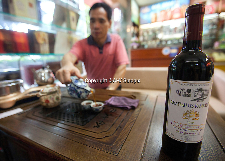 A wine trader pours tea next to a bottle of wine of indeterminate authenticity, in a shop that sells real and fake wine, Guangzhou, Guangdong Province, China, 18 July 2014. <br /> <br /> PHOTO BY SINOPIX